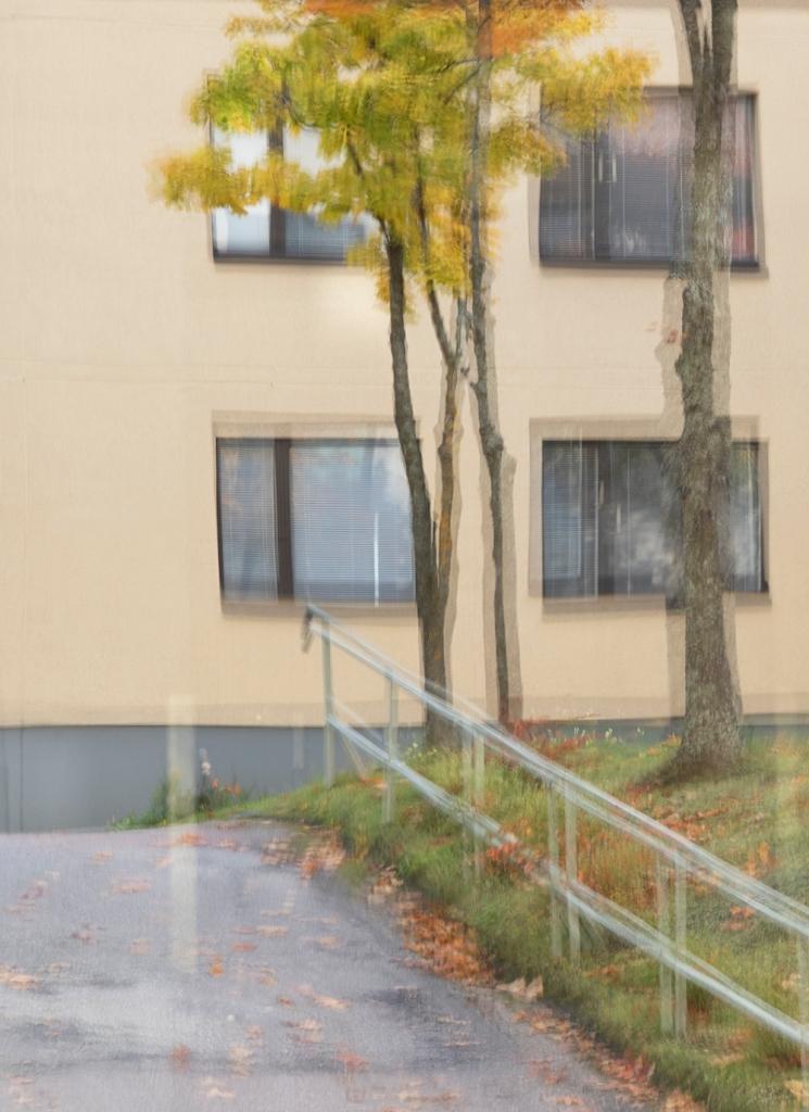 kerrostalon ikkunoita ja muutama puu näkyvät hieman epäselvänä heijastuksena toisesta ikkunasta