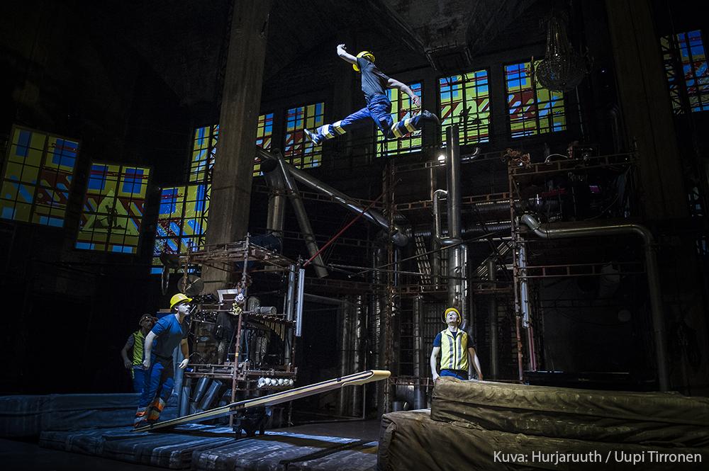 Sirkustaiteilijat ovat pukeutuneet rakennustyömiesten vaatteisiin ja taiteilevat keinulaudalla