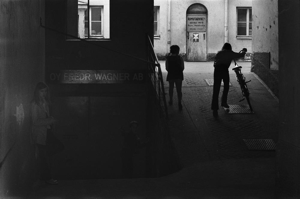 Lapsia Kalliossa porttikäytävässä, jossa Oy Fredr. Wagner Ab:n liike. Pihalla Romutarvike Oy:n ovi. Simo Rista / Finna.fi.